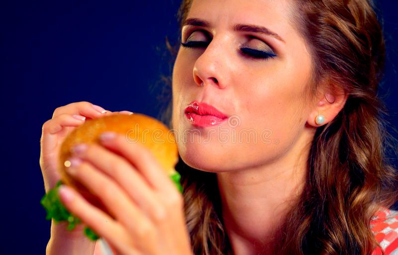 Woman edacity eat hamburger fast food. Woman eat hamburger fast food with keen appetite stock images