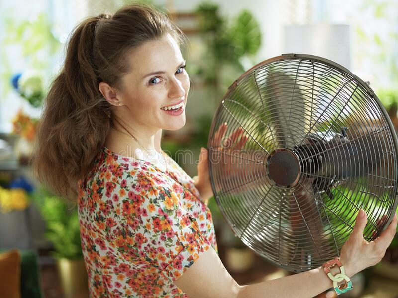 Woman with electric fan at modern home in sunny hot summer day royalty free stock photo