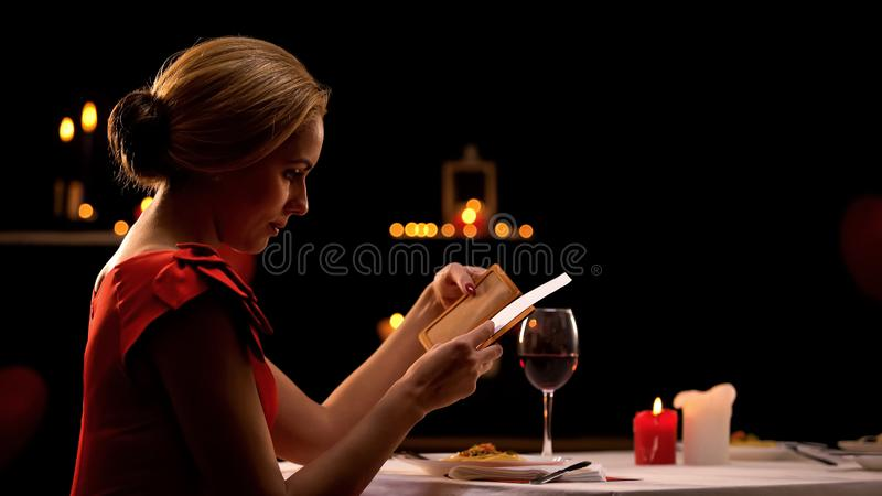 Woman in elegant dress looking at restaurant bill, having dinner alone, break up royalty free stock images