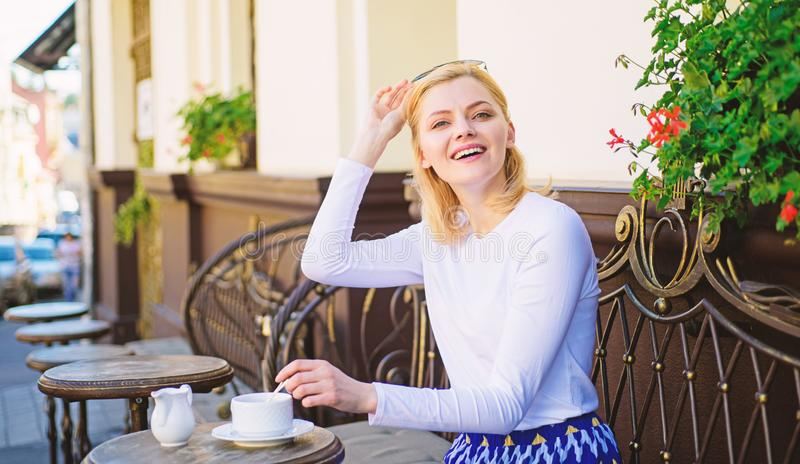 Woman elegant happy face have coffee cafe terrace outdoors. Mug of good coffee in morning gives me energy charge. Girl. Drink coffee every morning at same place stock image