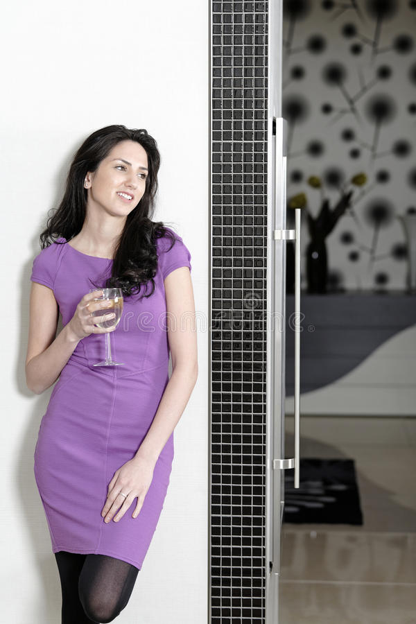 Woman in elegant kitchen. Attractive young woman in a dinner dress holding a glass of wine in her kitchen royalty free stock image