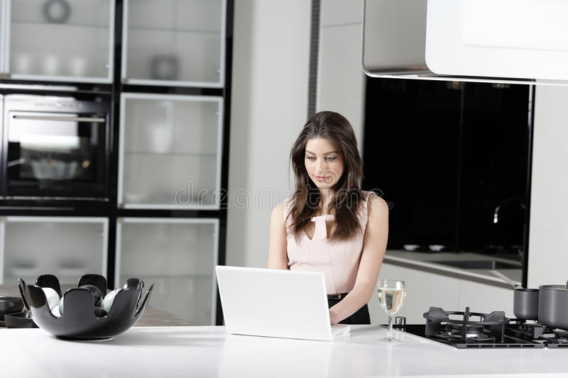 Woman in elegant kitchen. Attractive young woman in a dinner dress using a laptop stock photos