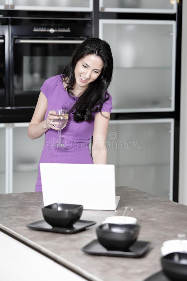 Woman in elegant kitchen. Attractive young woman in a dinner dress using a laptop stock photo