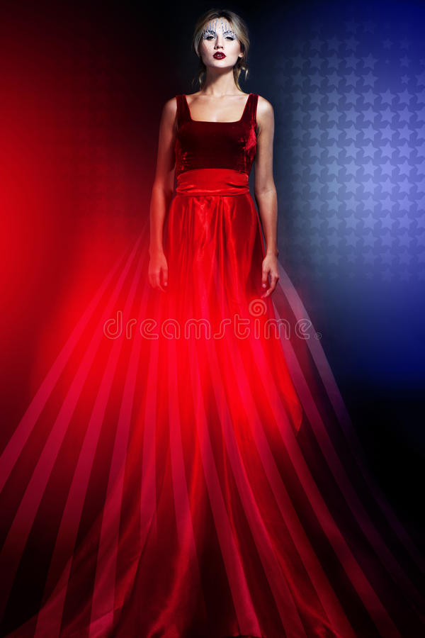 Woman in elegant red dress with American flag stock photography