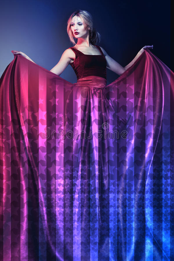 Woman in elegant red dress with American flag stock image