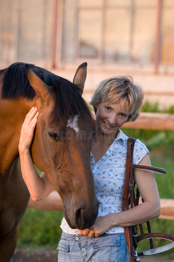 Woman embrace brown horse. Neck stock images