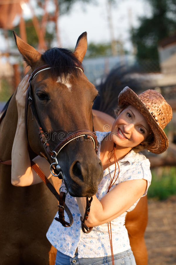 Woman embrace horse. Woman in hat embrace brown horse stock photography