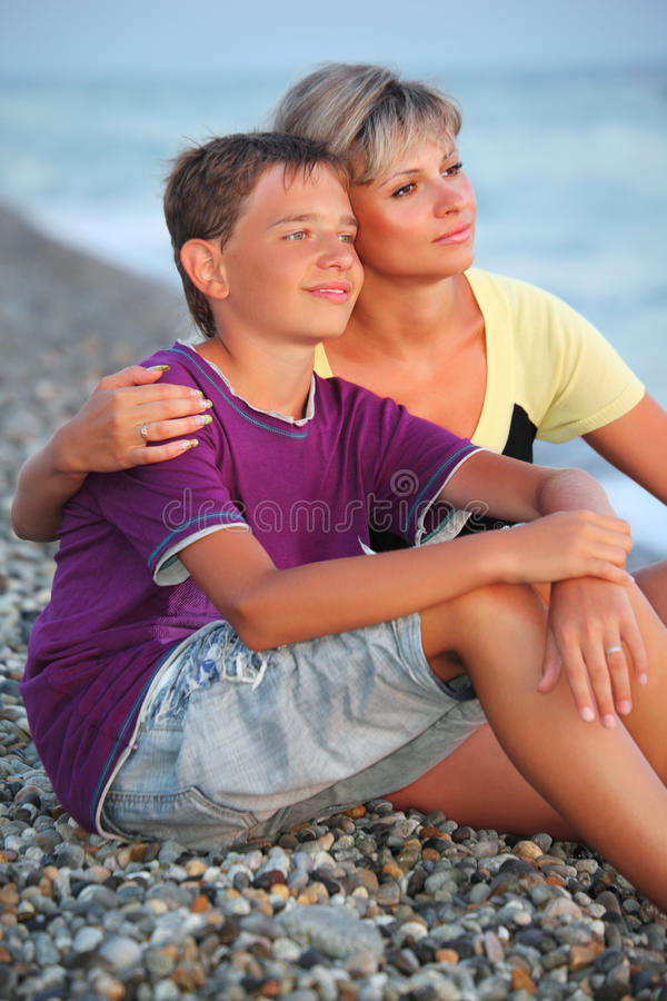 Woman embraces smiling boy on beach in evening