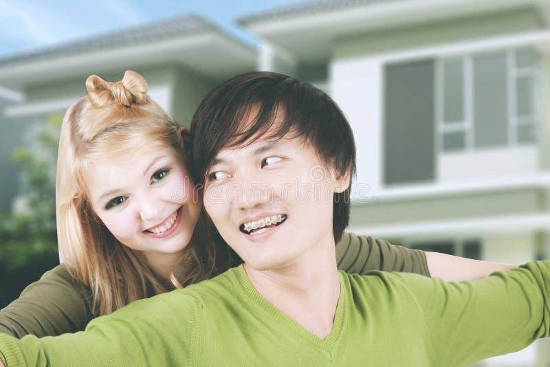 Woman embracing her husband near their house stock photos