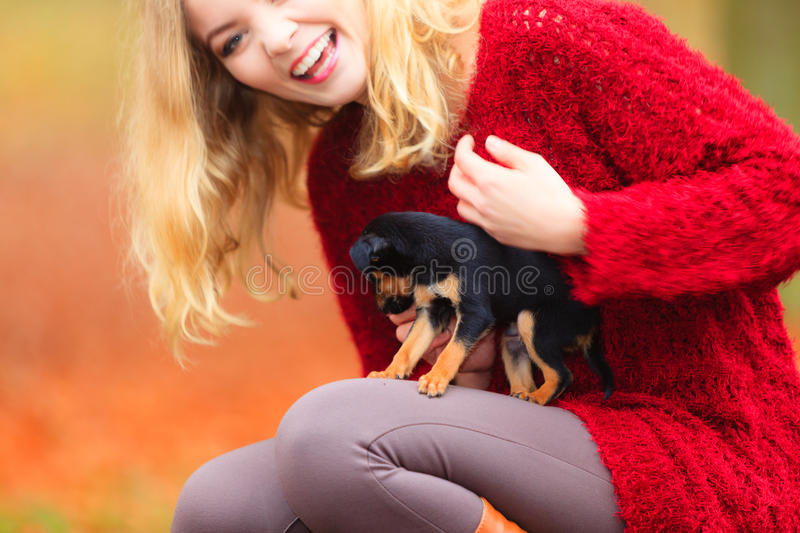Woman embrancing her puppy dog. Pets and people, pet adoption. Woman playing with her little dog pet outdoor, hugging lovingly embraces her puppy royalty free stock photography