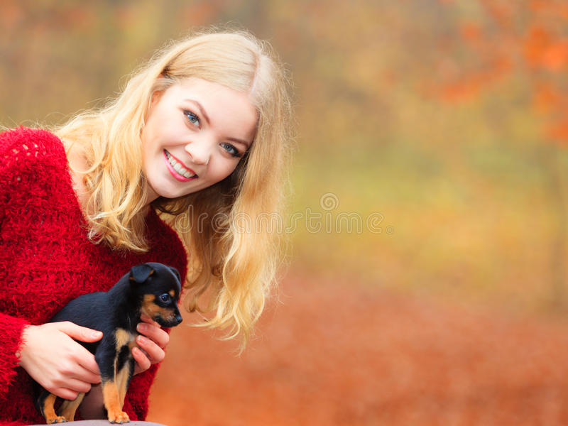 Woman embrancing her puppy dog. Pets and people, pet adoption. Woman playing with her little dog pet outdoor, hugging lovingly embraces her puppy royalty free stock image
