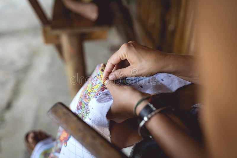 Woman embroider a serviette on knee. Hands and material visible royalty free stock images