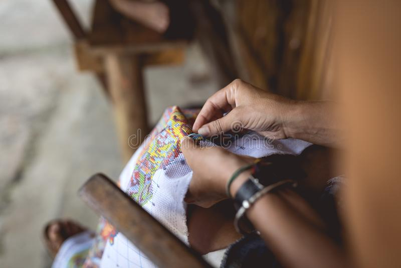 Woman embroider a serviette on knee. Hands and material visible stock photos