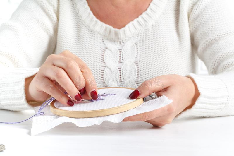 Woman embroidering cross lavender stock photos