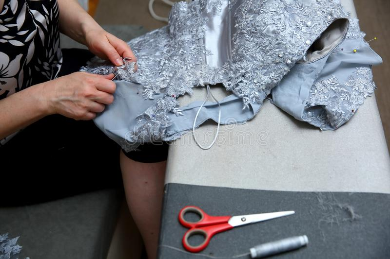 A woman embroidering a handmade dress. Today, tailoring can be called as an artistic profession. Every tailor shop, even the most modern one, will not be able royalty free stock image