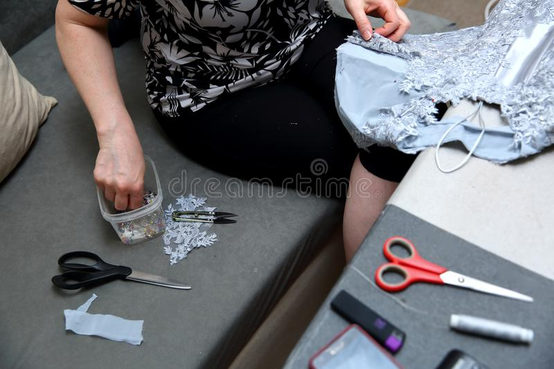 A woman embroidering a handmade dress. Today, tailoring can be called as an artistic profession. Every tailor shop, even the most modern one, will not be able stock images