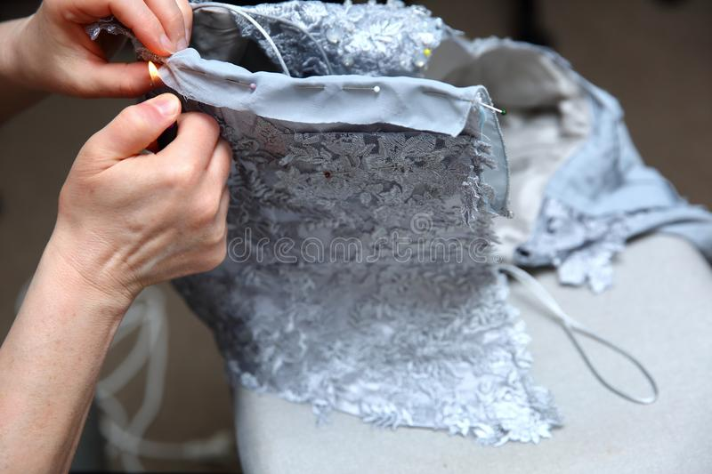 A woman embroidering a handmade dress. Today, tailoring can be called as an artistic profession. Every tailor shop, even the most modern one, will not be able royalty free stock photo