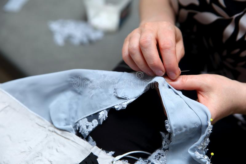 A woman embroidering a handmade dress. Today, tailoring can be called as an artistic profession. Every tailor shop, even the most modern one, will not be able stock photos