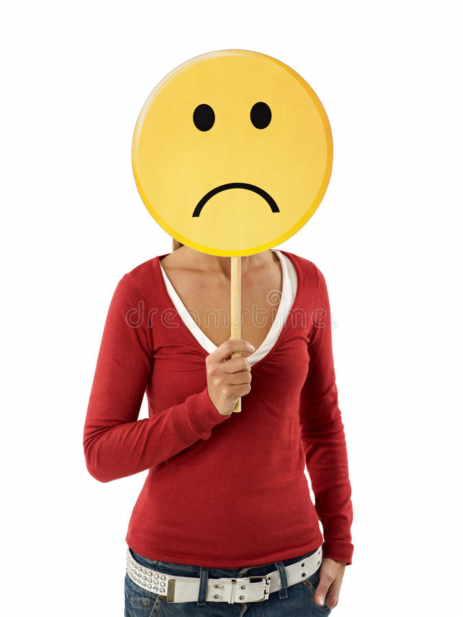 Woman with emoticon. Young adult woman holding sad emoticon on white background. Vertical shape, waist up royalty free stock image