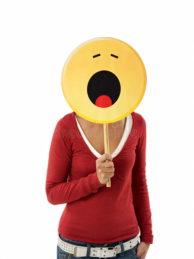 Woman with emoticon. Young adult woman holding emoticon, yawning on white background. Vertical shape, waist up stock photos