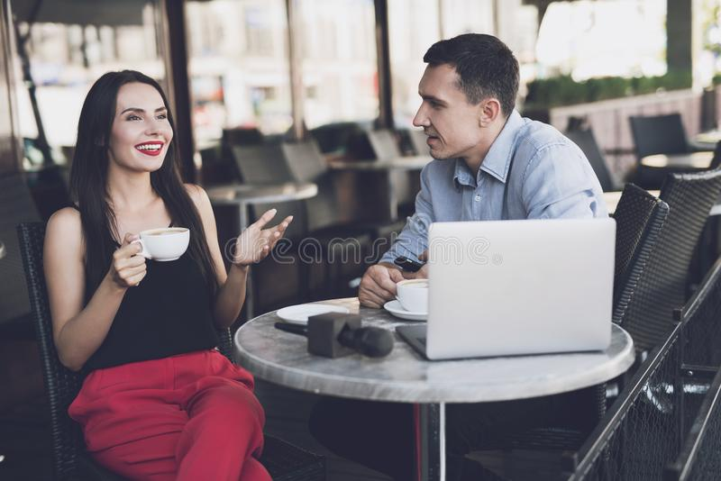 A woman emotionally answers the questions of a journalist. A journalist talks to a girl in a cafe. They drink coffee, there is a laptop and a microphone on the stock photography