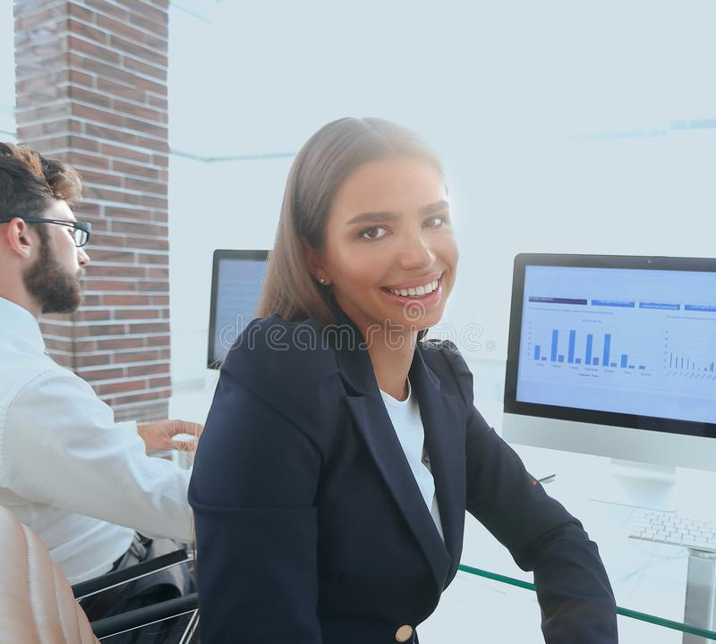 Woman employee and colleague sitting at the Desk. Close up of a woman employee and colleague sitting at the Desk in the office stock photo
