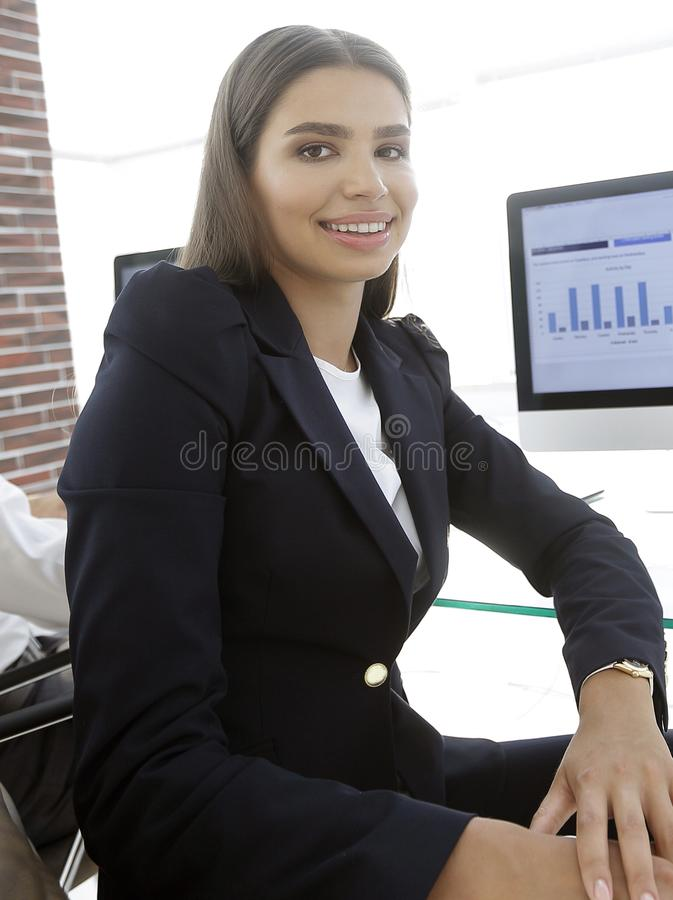 Woman employee and colleague sitting at the Desk. Close up of a woman employee and colleague sitting at the Desk in the office stock photography