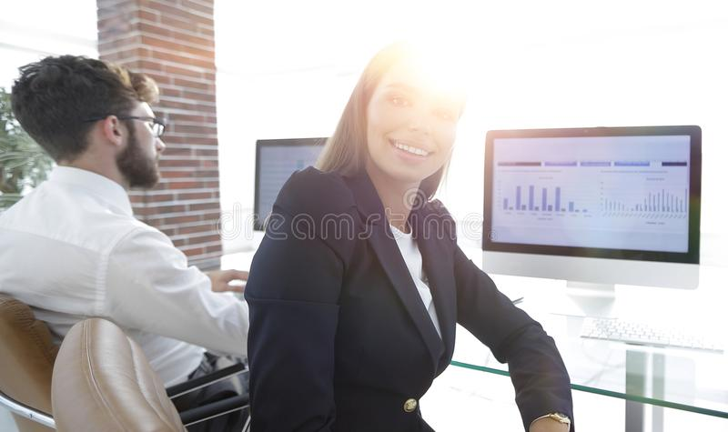Woman employee and colleague sitting at the Desk. Close up of a women employee and colleague sitting at the Desk in the office stock photo