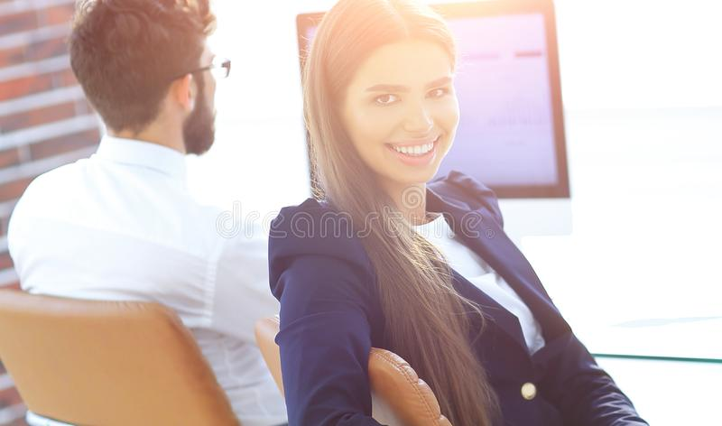 Woman employee sitting at a Desk. And looking at camera stock image