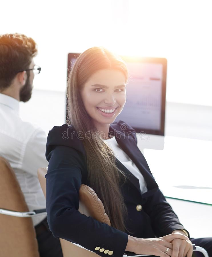 Woman employee sitting at a Desk. And looking at camera royalty free stock photography