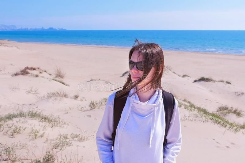 Portrait of young woman traveller with backpack on sea sand beach on vacation. royalty free stock photo