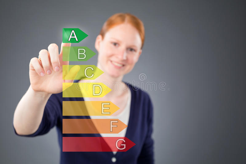 Woman with Energy Label for Efficiency. A young female consumer or businesswoman selecting top level efficiency from an energy or emissions label stock photos