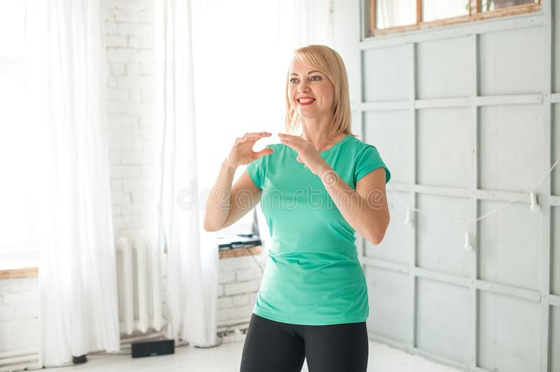 A woman is engaged in Chinese martial art in the studio. Woman and Tai Chi.  royalty free stock image