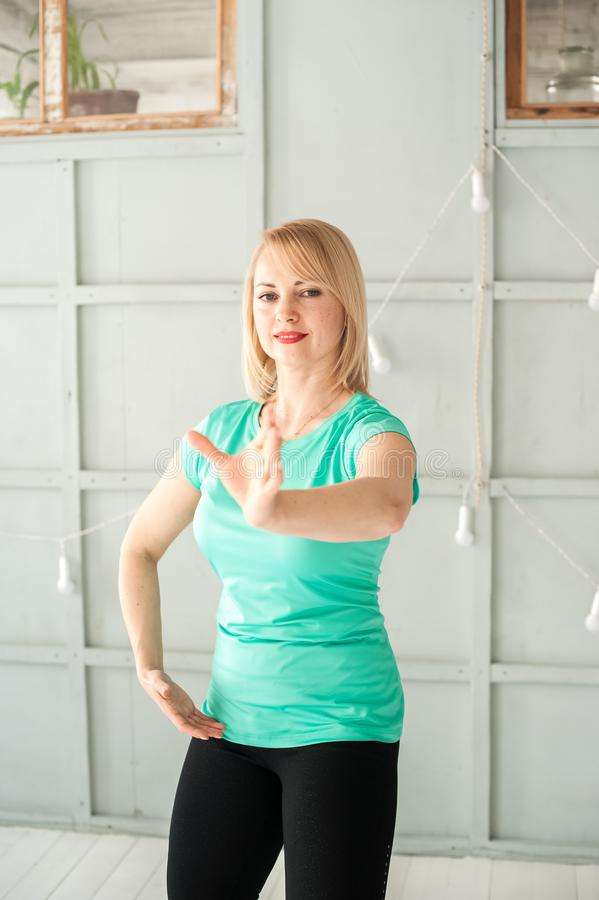 A woman is engaged in Chinese martial art in the studio. Woman and Tai Chi.  stock image