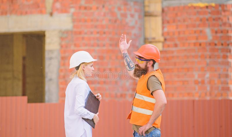 Woman engineer and bearded brutal builder discuss construction progress. Construction project management. Building. Industrial project. Discuss progress project royalty free stock photography