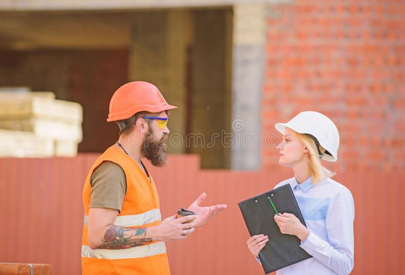 Woman engineer and bearded brutal builder discuss construction progress. Relationships construction client and stock images