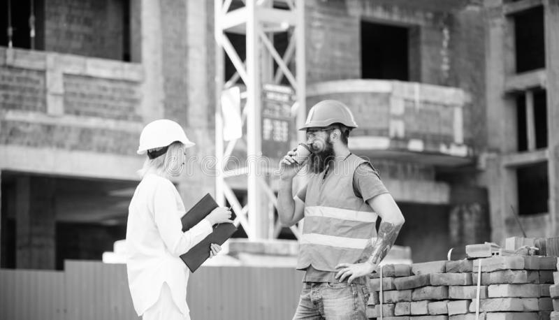 Woman engineer and brutal builder communicate construction site background. Construction team communication concept royalty free stock image