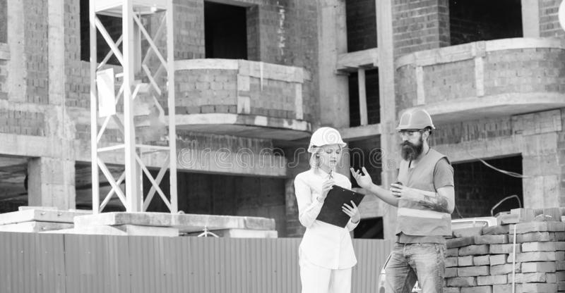 Woman engineer and builder communicate at construction site. Construction team communication concept. Relationships stock photography