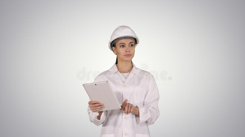 Woman engineer checking information and objects on her tablet on gradient background. stock photography