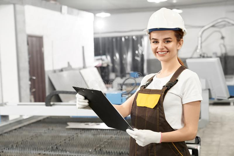 Woman engineer in helmet and coveralls posing in factory. Female engineer of factory standing near plasma laser cutter. Beautiful woman wearing in white helmet stock photos