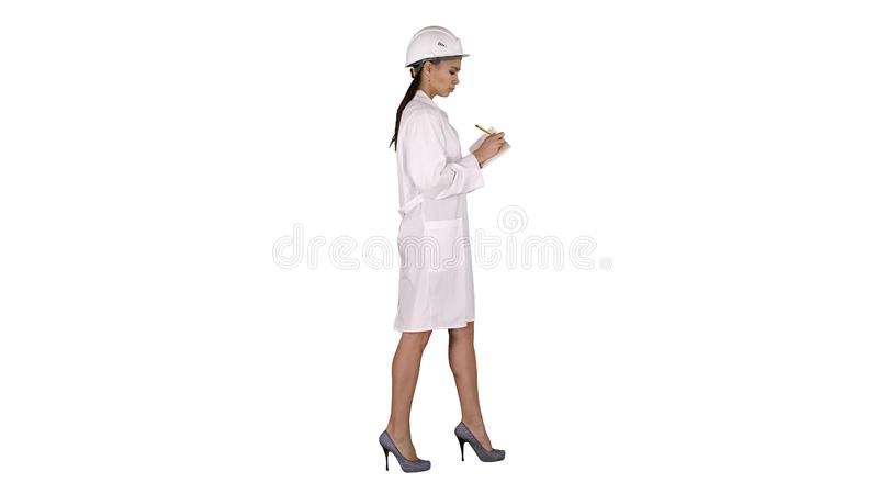 Woman engineer with helmet is holding pen and checklist putting something down while walking on white background. royalty free stock photo