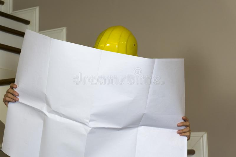 Woman engineer with safety helmet reading blueprint at construction site, checking work progress. royalty free stock photo