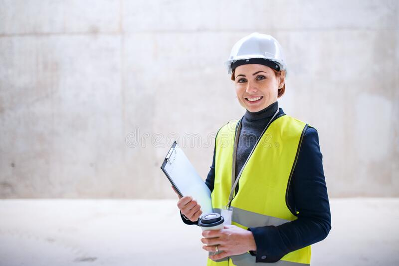 A woman engineer standing against concrete wall on construction site. Copy space royalty free stock photos
