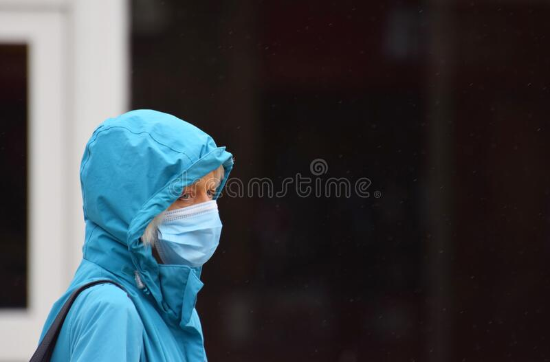 A woman in an English town centre wearing a face mask in public on the weekend that wearing face coverings became law in Englan stock photo