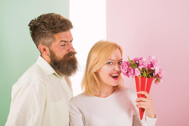 Woman enjoy fragrance bouquet flowers. Man with beard takes care about girlfriend happiness. Lady likes flower husband. Gifted her. Flowers delivery concept royalty free stock photography