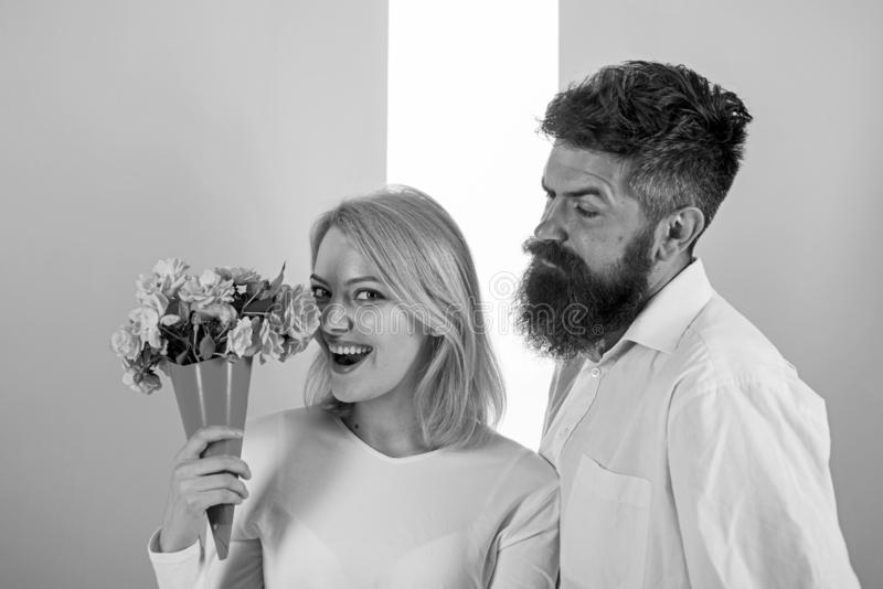 Woman enjoy fragrance bouquet flowers. Man with beard takes care about girlfriend happiness. Lady likes flower husband. Gifted her. Flowers delivery concept stock photography