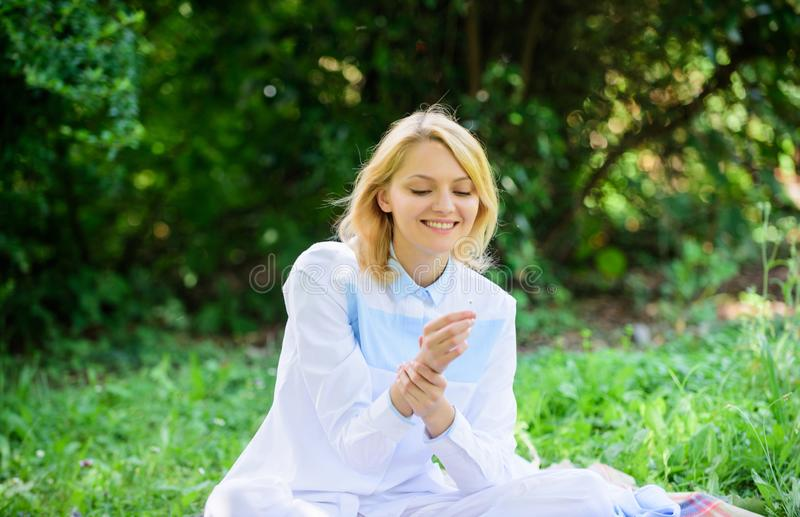 Woman enjoy relax nature background. Lady enjoy tender flower fragrance. Femininity and tenderness. Girl tender blonde. Sniff tiny flower while sit on green stock image