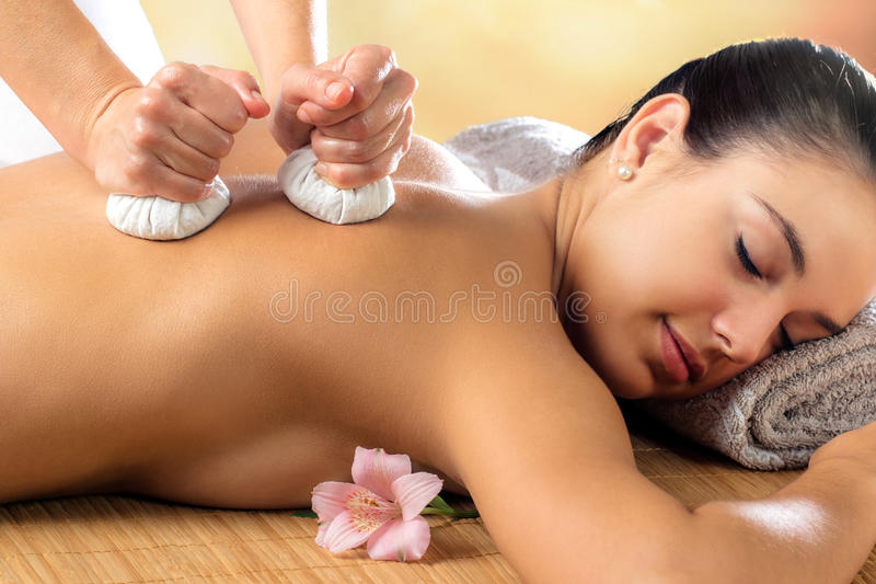 Woman enjoying aromatic pinda massage. royalty free stock images