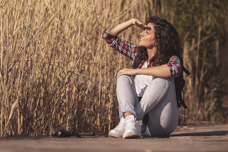 Woman enjoying autumn dayin nature. Woman sitting on the wooden lake docks, taking a break from hiking in nature, relaxing and enjoying a sunny autumn day royalty free stock photos