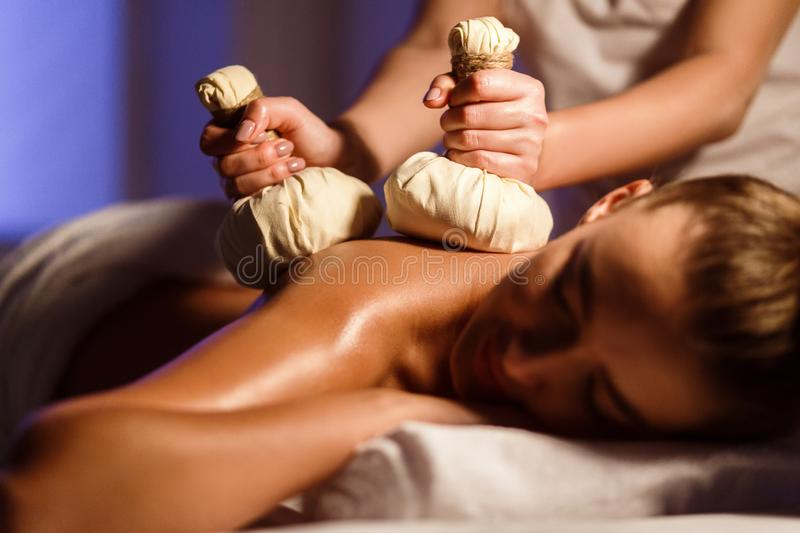 Woman enjoying back herbal massage at spa center royalty free stock images